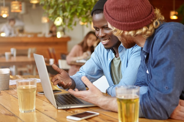 Zwei stilvolle männliche unternehmer verschiedener rassen trinken bier, während sie ein geschäftstreffen an der bar abhalten, über ein gemeinsames start-up-projekt diskutieren, über strategien und zukünftige pläne mit einem laptop sprechen