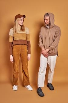 Zwei stilvolle mann und frau schauen sich studierend an und tragen trendige kleidung