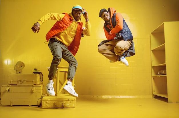 Zwei stilvolle rapper mit goldschmuck im coolen studio, hip-hop-darsteller mit gelber wand, trendige rap-sänger und breakdancer