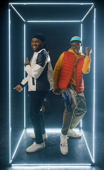 Zwei stilvolle rapper posieren im leuchtenden würfel, studio mit dunklem hintergrund