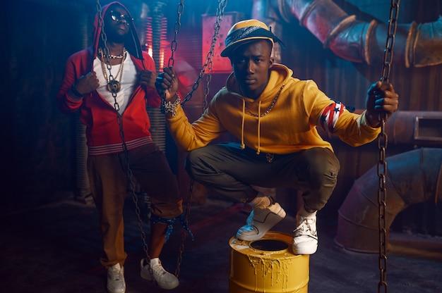 Zwei stilvolle rapper tanzen im studio mit cooler underground-dekoration