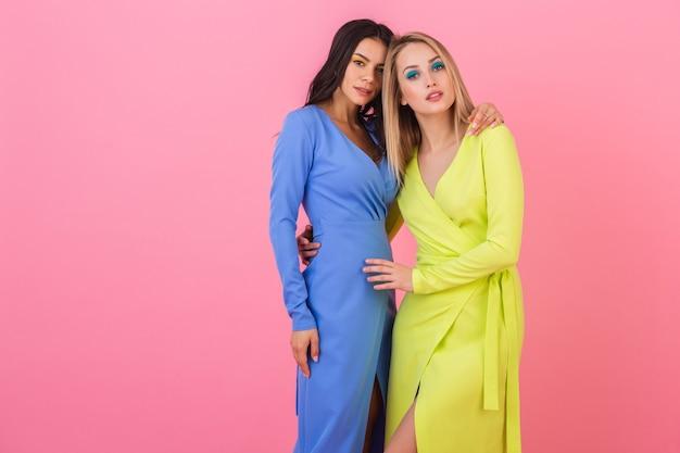 Zwei stilvolle sexy attraktive frauen, die auf rosa wand in stilvollen bunten kleidern der blauen und gelben farbe, frühlingsmodetrend aufwerfen
