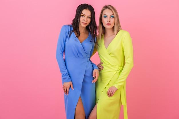 Zwei stilvolle sexy attraktive frauen, die auf rosa wand in stilvollen bunten kleidern der blauen und gelben farbe, sommermodetrend aufwerfen