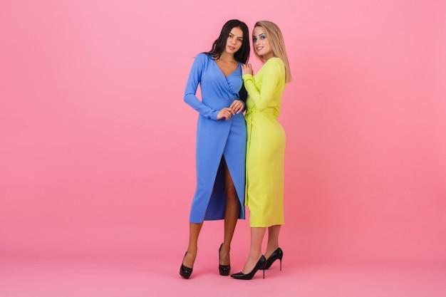 Zwei stilvolle sexy attraktive frauen, die volle höhe auf rosa wand in stilvollen bunten kleidern der blauen und gelben farbe, frühlingsmodetrend aufwerfen