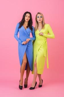 Zwei stilvolle sexy attraktive frauen, die volle höhe auf rosa wand in stilvollen bunten kleidern der blauen und gelben farbe, sommermodetrend aufwerfen