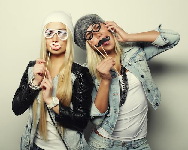 Zwei stilvolle sexy hipster-mädchen beste freunde bereit für die party, über grauem hintergrund