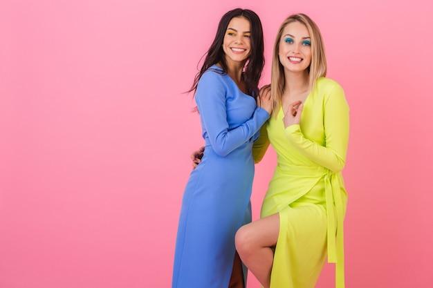 Zwei stilvolle sexy lächelnde attraktive frauen, die auf rosa wand in stilvollen bunten kleidern der blauen und gelben farbe, sommermodetrend aufwerfen