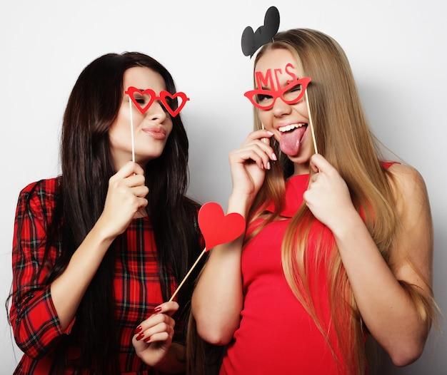Zwei stilvolle sexy mädchen beste freunde, die rotes kleid bereit für party tragen
