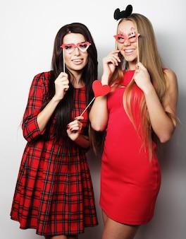 Zwei stilvolle sexy mädchen beste freunde tragen rotes kleid bereit für die party, über weißem hintergrund