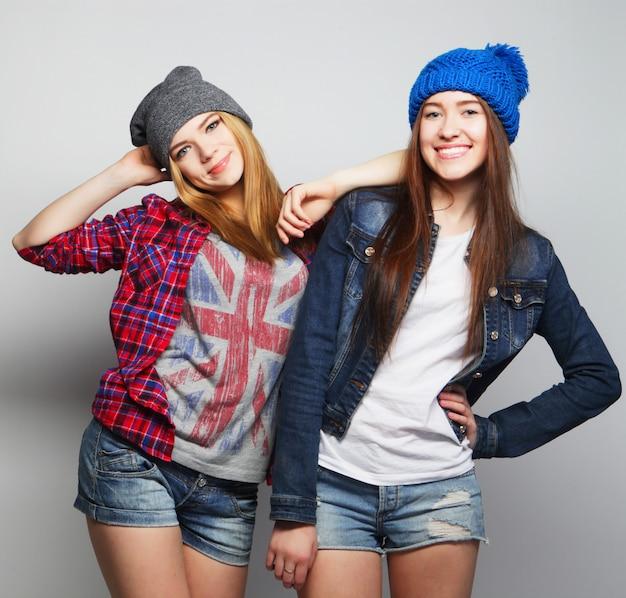 Zwei stilvolle teenager-mädchen, die mit hüten aufwerfen