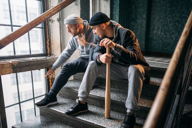 Zwei straßenbanditen mit baseballschläger warten auf opfer. kriminelle, raubgefahr, gefährliche typen