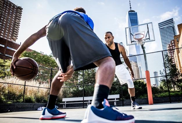 Zwei straßenbasketballspieler spielen hart auf dem platz