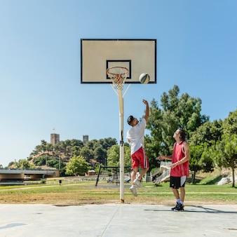 Zwei straßenspieler, der basketball spielt