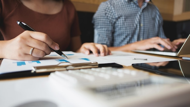 Zwei studenten arbeiten zusammen mit laptop und essay dokumente in einem café / bibliothek
