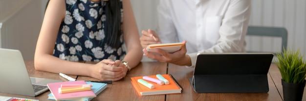 Zwei studenten beraten sich zu ihrer diplomarbeit auf einem holztisch