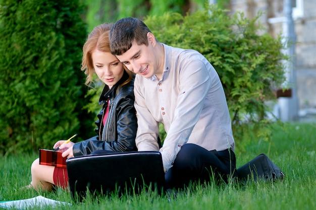 Zwei studenten, die auf dem gras im campus sitzen und studieren