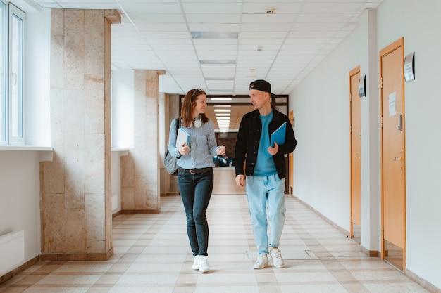 Zwei studenten, ein mann und ein mädchen, gehen den korridor der universität entlang und diskutieren lehrmaterial Premium Fotos
