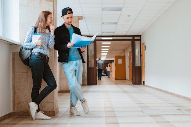 Zwei studenten, ein mann und ein mädchen, gehen den korridor der universität entlang und diskutieren lehrmaterial