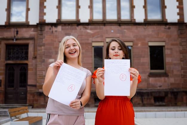 Zwei studenten in der nähe der universität mit testergebnissen