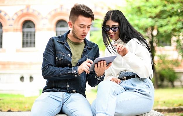Zwei studenten lernen zusammen mit einem digitalen tablet, das auf einer bank im freien sitzt