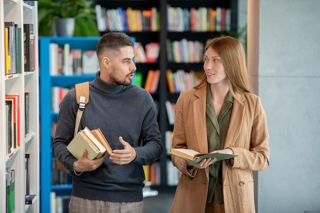 Zwei studenten oder kollegen diskutieren neugieriges buch in der bibliothek