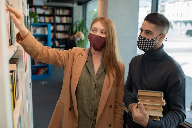 Zwei studenten oder kollegen in schutzmasken wählen bücher aus