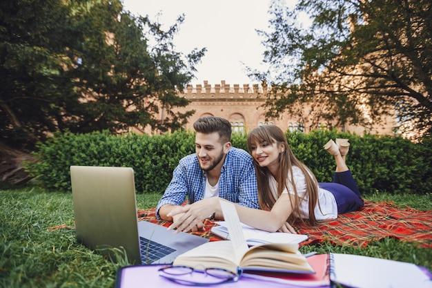 Zwei studenten sitzen auf dem grascampus und arbeiten an einem laptop. schönes mädchen und hübscher junge in der universität