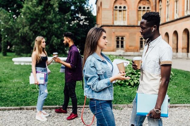 Zwei studenten sprechen in der nähe der universität auf dem campus