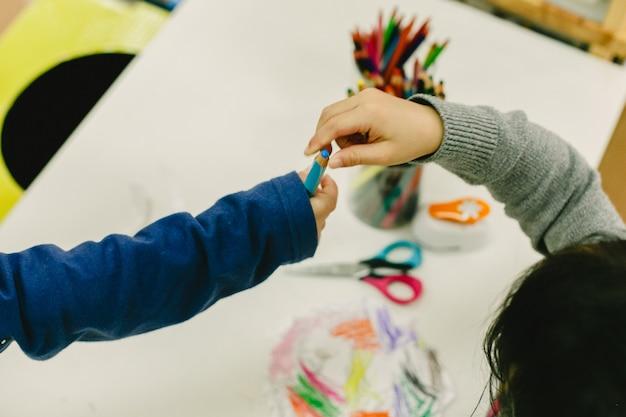 Zwei studenten teilen sich bleistifte in einem kindergarten