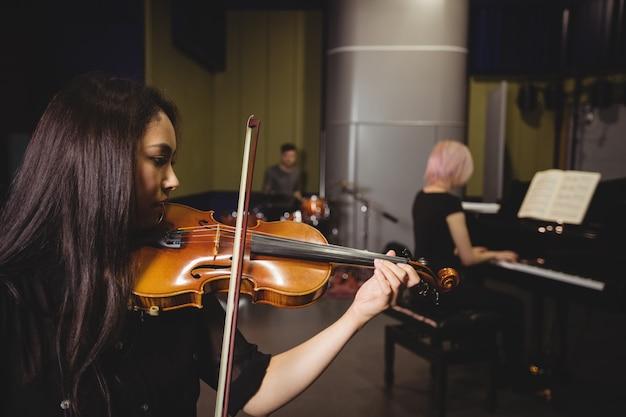 Zwei studentinnen, die geige und klavier spielen