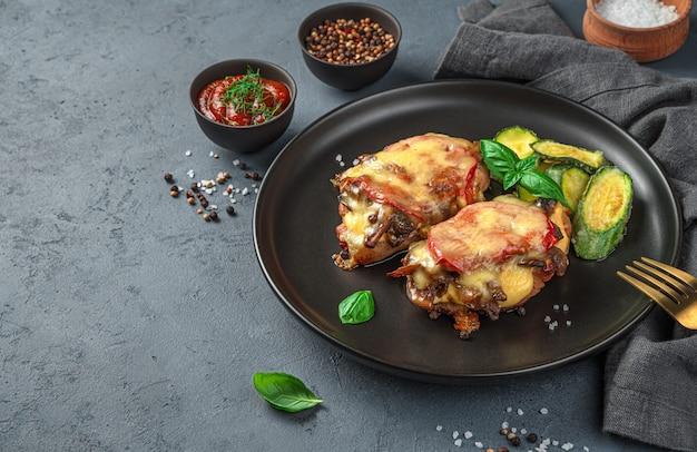 Zwei stück gebackenes fleisch mit champignons, tomaten und käse und einer beilage zucchini. in einem schwarzen schild auf grauem hintergrund. seitenansicht, platz zum kopieren.