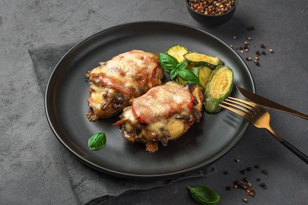 Zwei stück gebackenes fleisch mit gemüse und einer beilage aus zucchini auf dunkelgrauem hintergrund. seitenansicht, horizontal.