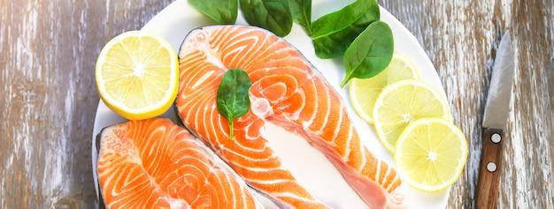 Zwei stücke frisches lachssteak auf einem weißen teller mit spinat und zitrone, auf grauem holzhintergrund. omega-3-vitamin, gesunder lebensstil. natürliches vegetarisches essen. ansicht von oben.