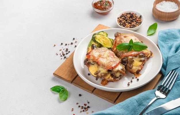 Zwei stücke gebackene hühnerbrust mit pilzen, tomaten und käse mit einer beilage aus zucchini auf hellgrauem hintergrund. seitenansicht, platz zum kopieren.