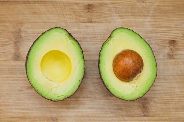 Zwei stücke geschnittene avocado auf hölzernem hintergrund. draufsicht auf reife avocado.