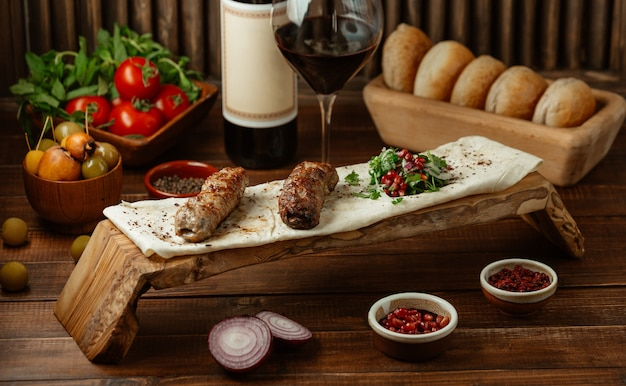Zwei stücke lule-kebab-grill, serviert mit arten und kräutern