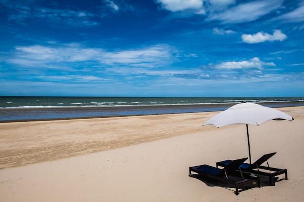 Zwei stuhl und sonnenschirm am strand mit blauem himmel