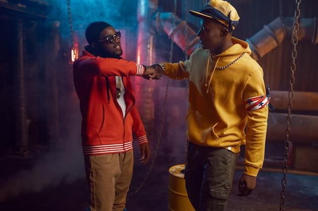 Zwei stylische rapper, breakdance im studio mit cooler underground-dekoration