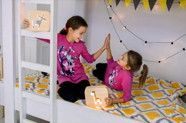 Zwei süße 10-jährige schwestern im hellen pyjama, die herumalbern, spielen und spaß im stilvollen etagenbett haben, hölzerne nachtlampen halten und sich gegenseitig hohe fünf geben.