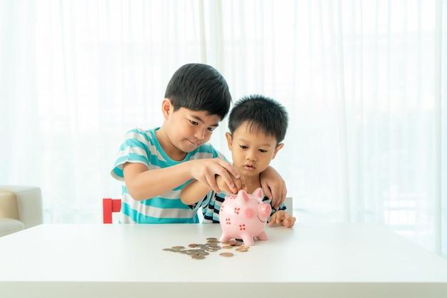 Zwei süße asiatische brüder werfen zusammen eine münze in ein sparschwein