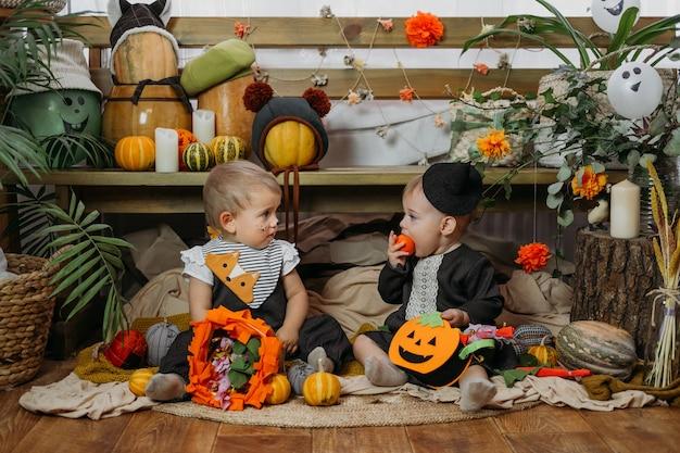 Zwei süße babymädchen in halloween-kostüm sitzen auf dem bett mit halloween-dekoration zu hause