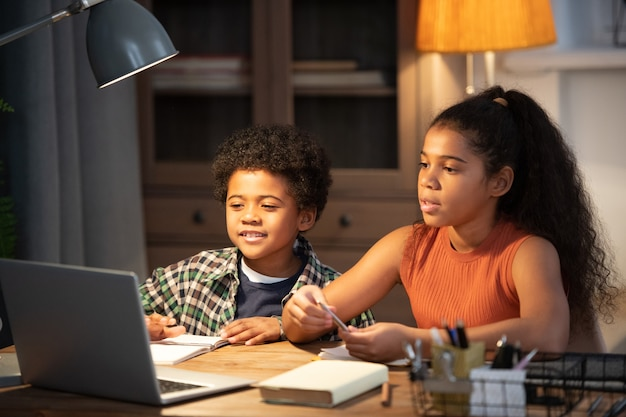 Zwei süße geschwister afrikanischer abstammung sitzen am tisch vor dem laptop und nehmen am online-unterricht teil, während sie den erklärungen des lehrers zuhören