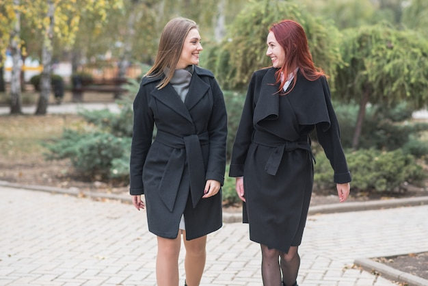 Zwei süße junge frauen gehen spazieren und reden über wichtige themen