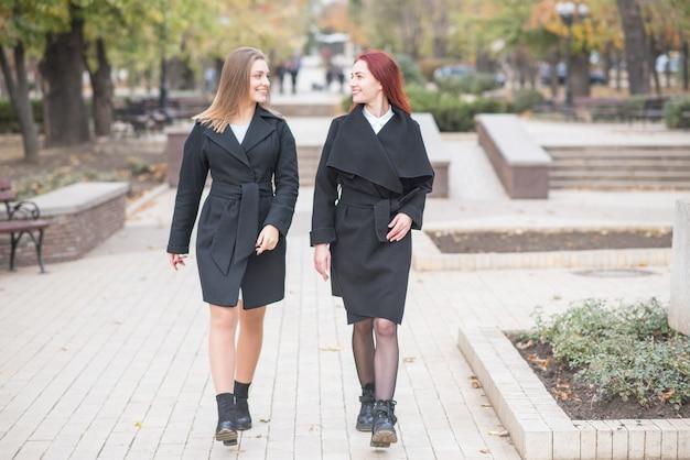 Zwei süße junge mädchen gehen spazieren und reden über wichtige themen