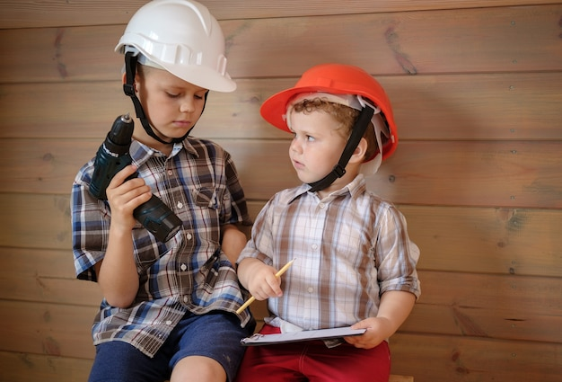 Zwei süße jungs in bauhelmen diskutieren einen plan für die bevorstehende arbeit. kinder spielen baumeister. kleiner junge mit einem schraubenzieher in den händen