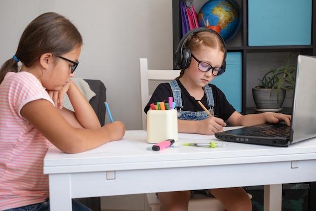 Zwei süße kaukasische mädchen in brillen mit laptop beim lernen zu hause. zurück zur schule