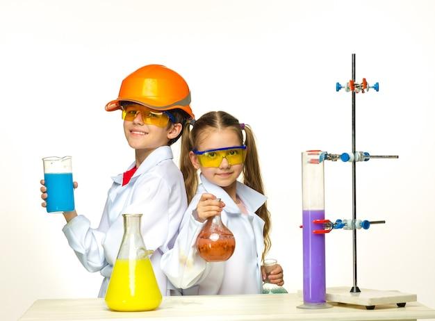 Zwei süße kinder im chemieunterricht machen experimente auf weißem hintergrund
