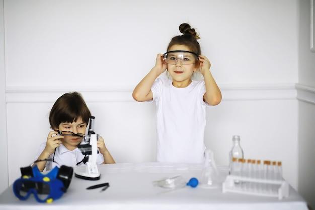 Zwei süße kinder im chemieunterricht machen experimente isoliert auf weißem hintergrund