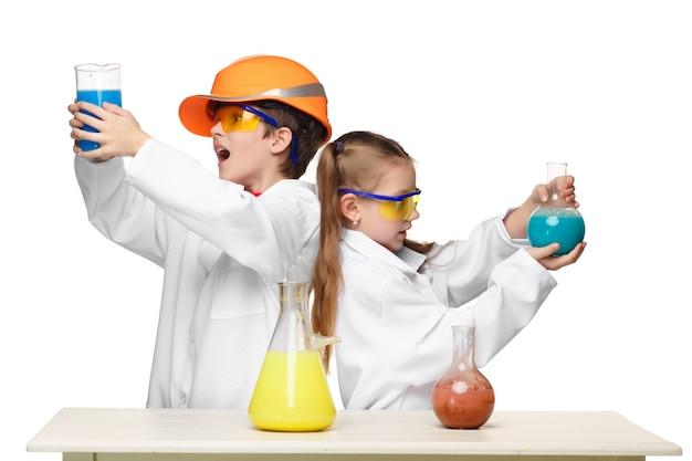 Zwei süße kinder im chemieunterricht machen experimente