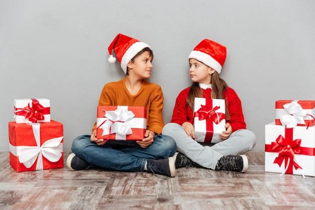 Zwei süße kinder in weihnachtsmann-hüten mit geschenkboxen
